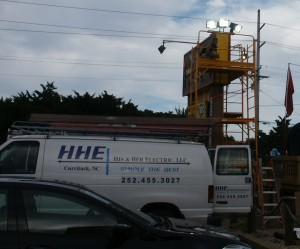 scaffold next to sign with building lights on top of sign
